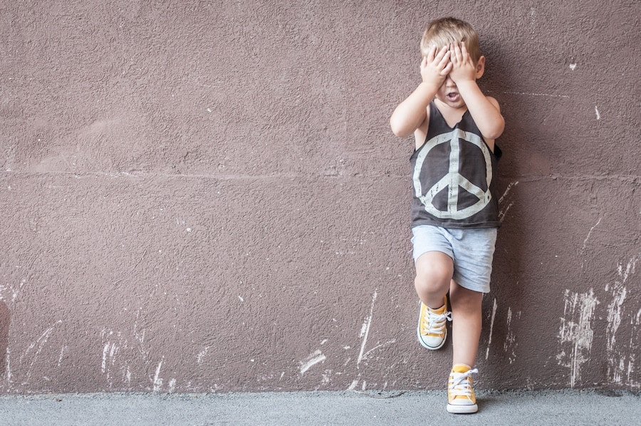 Sad boy over textured wall background with space for text