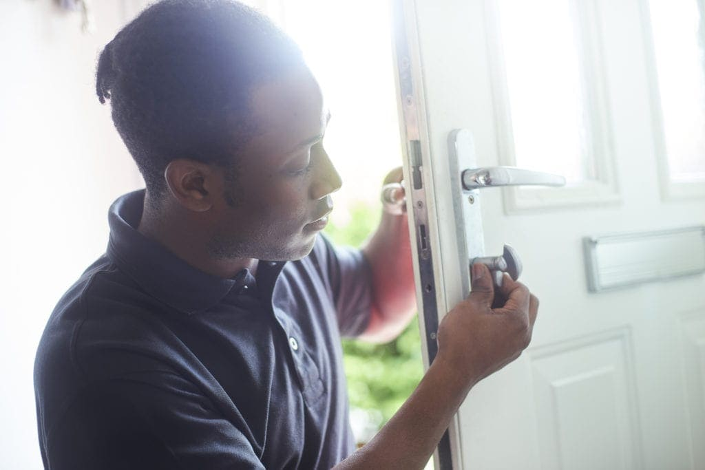 A young locksmith changing the lock on a residential front door.